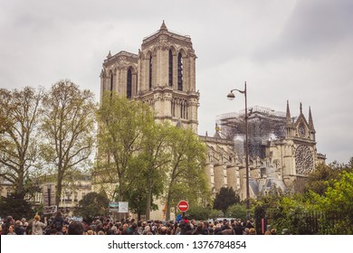 Paris, France - April 16th, 2019: Crowd standing in front of the Cathedral Notre Dame de Paris after the tragic fire of April 15th, 2019. The fire devastated large parts of the 850-year-old building.