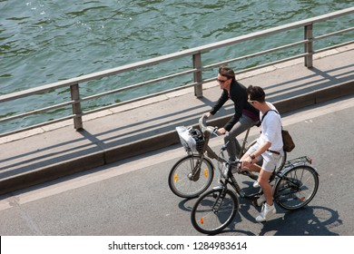 Paris, France - April 17, 2011: A group of people riding bicycles along the river embankment Genre