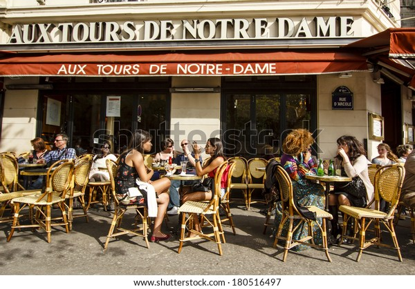 """PARIS, FRANCE - APRIL 17 : People chatting over drinks enjoing first spring sun in the cafe """"Aux Tours de Notre Dame"""" near Notre-Dame cathedral on April 17th, 2013 in Paris, France"""
