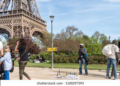 Paris, France - April 18, 2018: Peddler, selling miniatures of the Eiffel Tower next to the real monument