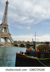 paris, france - april 20 2019 : house boat with small liberty statue docked on the right quat of Seine river. Eiffel twoer in the background