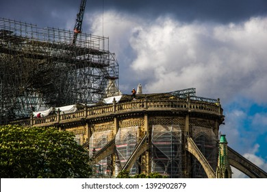 PARIS, FRANCE - April, 2019 : Workers at the north gable of Notre Dame de Paris reinforced by wooden structures after fire that started in the attic during works on the roof