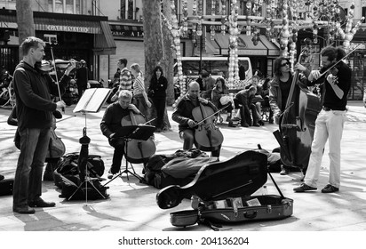PARIS, FRANCE - APRIL 21, 2014: String sextet plays at Comedie Francaise square before the audience consisting mainly of tourists. Dozens buskers perform on the streets and in metro of Paris.