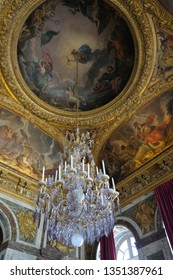 Paris, France - April 21, 2018: Sumptuous chandelier and ceiling in palace of Versailles
