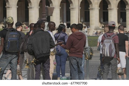 PARIS, FRANCE - APRIL 22:  A gathering of illegal immigrants touting trinkets to tourists outside the Louvre in Paris, France on the 22nd April, 2015.