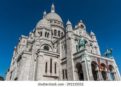 PARIS, FRANCE - APRIL 23, 2015: Tourists stroll in Montmartre near Basilica Sacre Coeur (designed by Paul Abadie, 1914) - Roman Catholic Church and minor basilica, dedicated to Sacred Heart of Jesus.