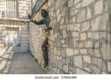 "PARIS, FRANCE -APRIL 23, 2015: Jean Marais sculpture ""Le Passe-Muraille"" (Man Who Walked through Walls, 1989) on Montmartre. Le Passe-Muraille is the title of a story by Marcel Ayme."