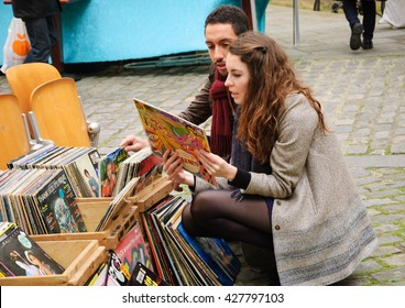PARIS, FRANCE - APRIL 23, 2016: Unidentified young couple choosing vinyl records (A Collection Of Beatles Oldies album) at flea market.