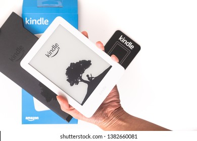PARIS, FRANCE - APRIL 25, 2019:  Amazon kindle basic 2019 unboxing on white background