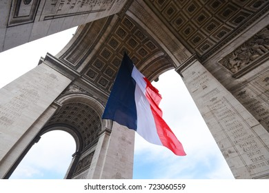 Paris, France - April 26, 2016 - The Arc de Triomphe detail and a France flag waving in Paris