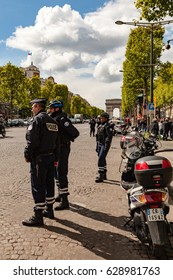 Paris, France - April 26, 2017 : Police officers blocking Champs Elysées in order to secure the funeral march in tribute to Xavier Jugelé killed by Islamic State few days before.