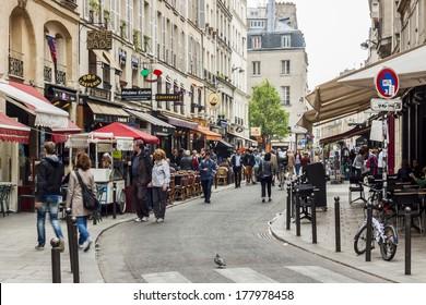 PARIS, FRANCE -  APRIL 26: Tourists walk past a cafeteria and souvenir store on april 26, 2013 in Paris. Paris is the most visited city in the world.