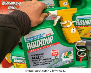 Paris, France - April 27, 2019: Customer buying roundup in a french Hypermarket. Roundup is a brand-name of an herbicide containing glyphosate, made by Monsanto Company.