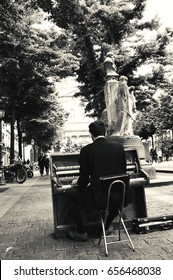 PARIS, FRANCE - APRIL 29, 2017: Street pianist playing music at Sorbonne square and mid aged couple walking towards him. Dozens buskers perform on the streets and in the metro of Paris.