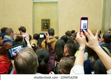 PARIS, FRANCE - APRIL 3, 2015: Tourists photographing the famous picture of Gioconda in Louvre Museum.