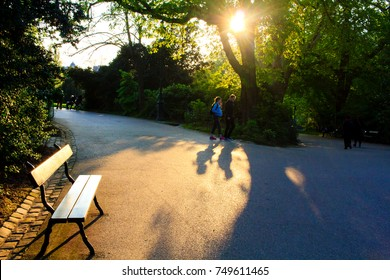 PARIS, FRANCE - APRIL 4th, 2017 : people passing on alleyways of the Buttes-Chaumont park in Paris, France. Sunset light creating deep shadows on the alley-ways.