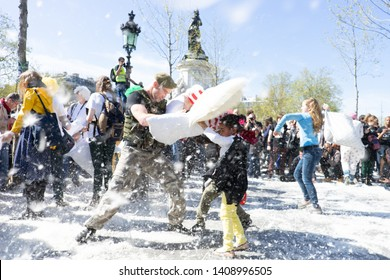 PARIS, FRANCE - APRIL 5, 2014 : Two girls fighting a soldier with pillow during the Pillow fight flashmob at the Place de la Republique