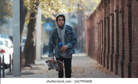Paris, France - April 5, 2018: Unrecognizable young rebellious teenage boy in jeans wear and balaclava walks with skateboard and can spray of paint down the street, stops to paint the street wall