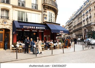 PARIS, FRANCE - APRIL 6, 2019: Parisians and tourists sit on terrace of Etienne Marcel cafe at Montmartre street. Cafes in Paris appear to be an important cultural and socializing institutions.