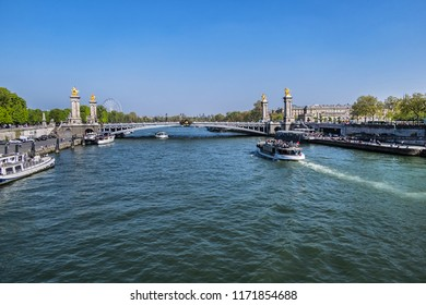 PARIS, FRANCE - APRIL 8, 2017: Seine River and famous Alexandre III Bridge. Bridge, with its exuberant Art Nouveau lamps, cherubs, nymphs and winged horses at either end, was built in 1896 - 1900.