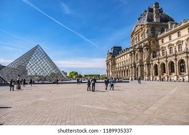 PARIS, FRANCE - APRIL 8, 2017: Paris Louvre Museum: main courtyard (Cour Napoleon) with pyramid and Louvre Museum buildings. Paris Louvre Museum is one of largest and most visited museums worldwide.