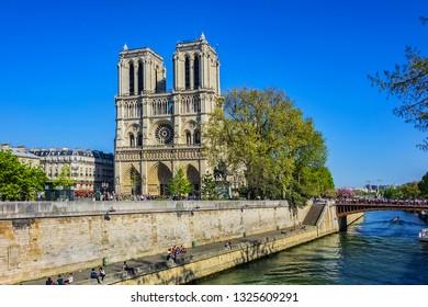 PARIS, FRANCE - APRIL 8, 2017: Embankment of the river Seine and Cathedral Notre Dame de Paris - a most famous Gothic, Roman Catholic cathedral (1163 - 1345).