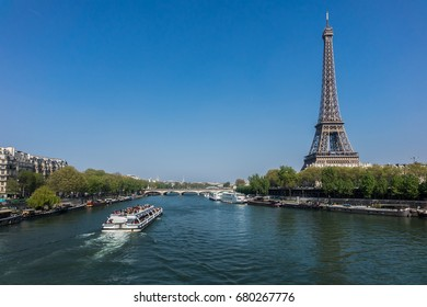 PARIS, FRANCE - APRIL 9, 2017: Tourists on outdoor excursion boats (Bateaux Mouches) watch the sights of Paris from the River Seine.