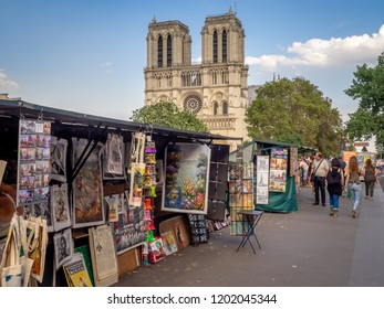 Paris, France - August 1, 2018: Traditional Bouquiniste booth on the edge of the Seine in front of the Notre-Dame cathedral. The Bouquinistes sell used and antique books as well as souvenirs.