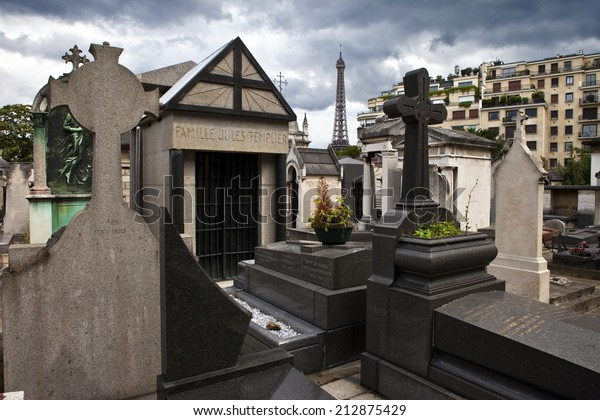 PARIS, FRANCE - AUGUST 10TH 2014: The historic Passy Cemetery in Paris on 10th August 2014.  The Eiffel Tower can be seen in the distance.