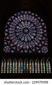 Paris, France - August 11, 2014: Colorful round stained glass window in dark interior of the Notre Dame de Paris cathedral