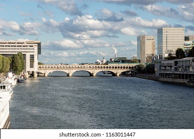 Paris, France - August 13, 2018: Metro crossing Bercy bridge with French Ministry for the Economy and Finance and National Library of France in background - Paris, France