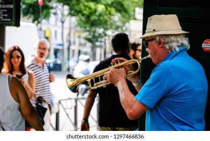 PARIS, FRANCE - AUGUST 15, 2013: Senior musician plays trumpet near Church of Saint-Germain-des-Pres. Dozens buskers perform on the streets and in the metro of Paris.