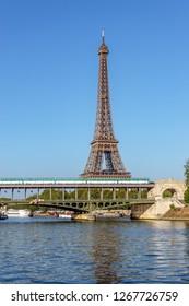 Paris, France - August 15, 2018: Metro crossing Bir-hakeim bridge with Eiffel Tower in background - Paris, France