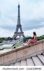 Paris / France - August, 17 2018, Woman looking the Eiffel Tower in cloudy day