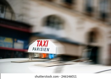 PARIS, FRANCE - AUGUST 18, 2014: Taxi sign on top of a cab vehicle in motion as seen in Paris, France
