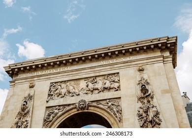 "PARIS, FRANCE - August 18, 2014: Porte Saint-Denis triumphal arch with the entablature bronze inscription LUDOVICO MAGNO, ""To Louis the Great"". Built in 1672 and designed by architect Francois Blondel"