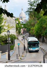 Paris / France — August 18, 2015: a RATP bus on the hill of Montmartre, Paris, France, with the dome of Sacre-Coeur basilica in the background