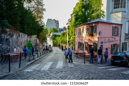 Paris / France — August 18, 2015: a cobbled street in Montmartre district of Paris, France, with La Maison Rose, or the Pink House, a famous restaurant visited by Picasso, at sunset