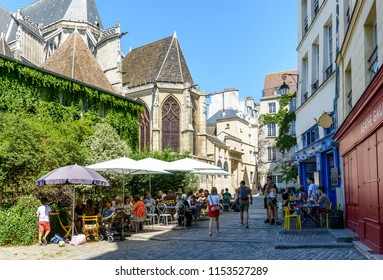 Paris, France - August 2, 2018: A small pedestrian cobbled street in the old district of Le Marais, behind Saint-Gervais church, with people having lunch on the shady terrace of a restaurant.