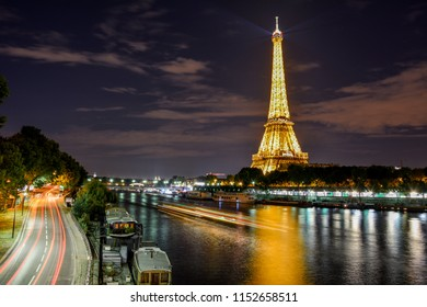 Paris / France — August 20, 2015: evening panorama of the Seine with the illuminated Eiffel Tower from Pont de Bir-Hakeim. The light show on the tower, organised every day, attracts a lot of tourists