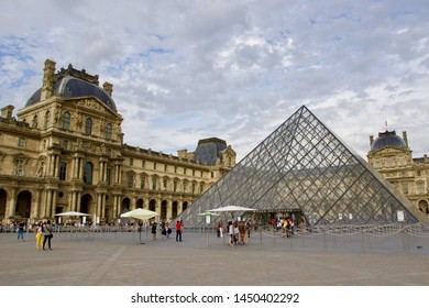 PARIS, FRANCE - AUGUST 2018: tourists entering the pyramid of glass that is the entrance of Louvre museum in Paris one of the most important all over the world,