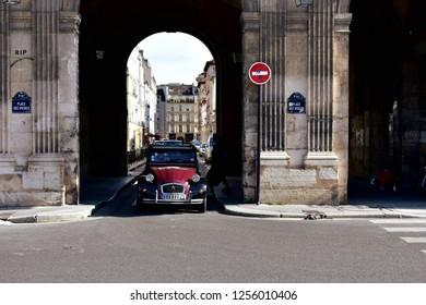 Paris, France, August 2018. A very old Citroen 2CV car runs in the oldest square of the city, Place des Vosges.