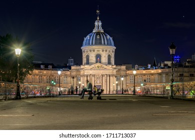 Paris, France. August 2019. Night time long exposure view of the Pont des Arts bridge and the illuminated Institut de France, grand cupola-topped building in baroque style.