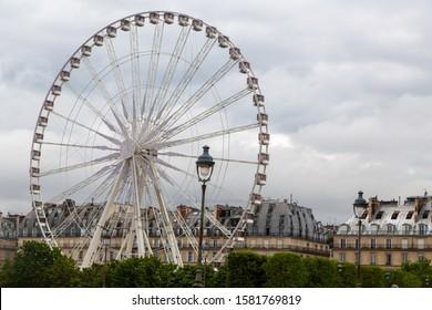PARIS, FRANCE. AUGUST, 2019. Ferris wheel (Roue de Paris) on the Place de la Concorde from the Tuileries Garden in a cloudy day