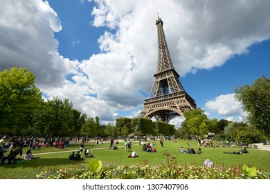 PARIS, FRANCE - AUGUST 21, 2014: Tourists enjoying a beautiful day in the surroundings of the Eiffel tower.