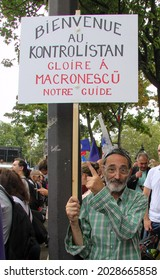 PARIS, FRANCE - AUGUST 21, 2021: Activist of the anti-Macron, anti-health passport policy during the manifestation. The poster says Welcome to Kontrolistan, the glory to Macronescu