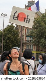PARIS, FRANCE - AUGUST 21, 2021: A Japanese activist of the anti-Macron, anti-health passport policy during the manifestation at Place Denfert-Rochereau. The poster says Liberty