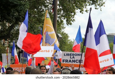 """PARIS, FRANCE - AUGUST 21, 2021: Activists of the anti-Macron, anti-health passport policy during the manifestation at Place Denfert-Rochereau. The poster says """"Let's free France"""""""
