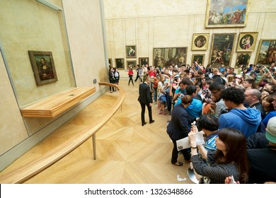 Paris, France - August 22, 2014: Tourists photographing the famous picture of Gioconda in Louvre Museum.