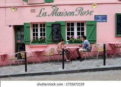 Paris, France -  August, 28 2011: А young couple playing cards on the La Maison Rose restaurant terrace in the Montmartre.